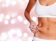 Frau klemmt Fett auf ihrem Bauch Lizenzfreies Stockfoto