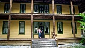 Frau klopft auf Tür des alten historischen Hauses Stockbild