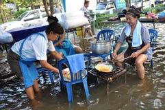Frau kochen freie Mahlzeiten für Flüchtlinge in einer überschwemmten Straße von Bangkok, Thailand, am 31. Oktober 2011 lizenzfreies stockfoto