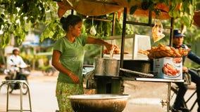 Frau kocht auf der Seite auf der Straße lizenzfreie stockfotos