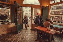 Frau kommen in alte Bar mit einigen trinkenden Männern und sitzen nahe Fenster Stockfoto