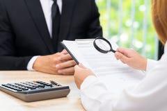 Frau kontrolliert anerkannten Darlehensvertrag mit Bankverkäufer stockbild