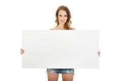 Frau kurz gesagt mit leerer Fahne Lizenzfreies Stockbild