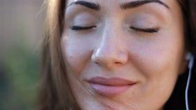 Frau in lächelnder und hörender Musik der Kopfhörer mit ihren Augen schloss im Freien stock video footage