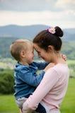 Frau lächelt an ihrem Sohn Lizenzfreie Stockfotos