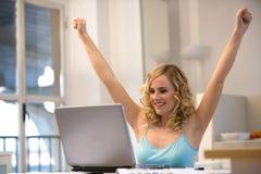 Frau am Laptop mit den Armen oben Stockbild