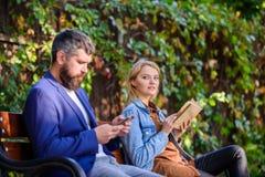 Frau las Buch, während Mann ebook Smartphone las Mann mit Bart und Frau lasen alternative Informationsspeicherung gelesen stockfotografie
