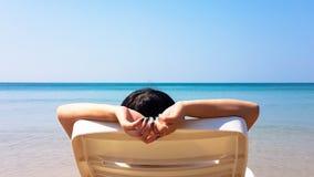 Frau legen auf den weißen Lehnsessel auf dem Strand Lizenzfreie Stockfotos