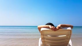 Frau legen auf den weißen Lehnsessel auf dem Strand Stockfotografie
