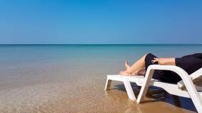 Frau legen auf den weißen Lehnsessel auf dem Strand Lizenzfreie Stockfotografie