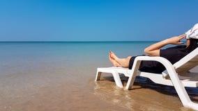 Frau legen auf den weißen Lehnsessel auf dem Strand Lizenzfreie Stockbilder