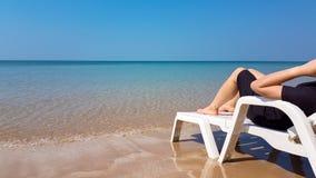 Frau legen auf den weißen Lehnsessel auf dem Strand Lizenzfreies Stockbild