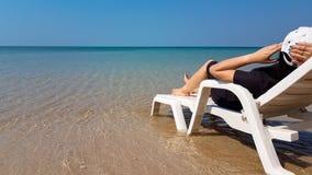 Frau legen auf den weißen Lehnsessel auf dem Strand Stockbild