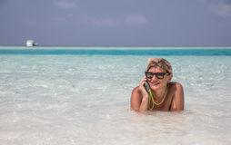 Frau legt in blaues Wasser vom Indischen Ozean und spricht per Telefon Stockfotografie