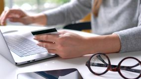 Frau leistet Online-Zahlung zu Hause mit einer Kreditkarte und einem Laptop stock footage