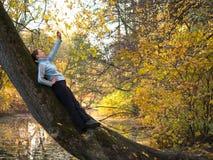 Frau liegend auf einem Baum und fotografiert Lizenzfreie Stockfotos