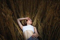 Frau liegt auf dem goldenen Gebiet des Weizens Lizenzfreie Stockfotos