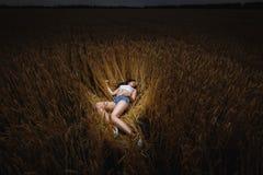 Frau liegt auf dem goldenen Gebiet des Weizens Lizenzfreies Stockfoto