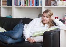 Frau liegt auf der Couch Lizenzfreie Stockfotos