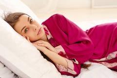 Frau liegt auf einem Bett Lizenzfreie Stockbilder
