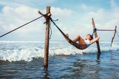 Frau liegt in der Hängematte über den Wellen und genießt mit Sonnenlicht stockfotos