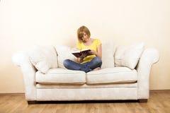 Frau liest auf einem Aufenthaltsraum lizenzfreie stockbilder