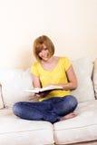 Frau liest auf einem Aufenthaltsraum stockfotografie