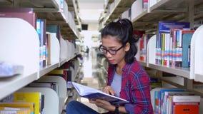 Frau liest Buch in der Bibliothek und im Lächeln stock video footage