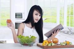 Frau liest Buch und bereitet Salat zu Stockbild