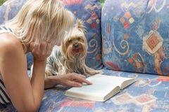 Frau liest ein Buch mit einem Yorkshire-Terrier Stockfotografie