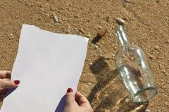 Frau liest eine Meldung von einer Flasche (schreiben Sie Text) stockfotografie