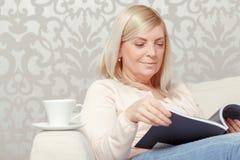 Frau liest Zeitschrift zu Hause Stockbilder