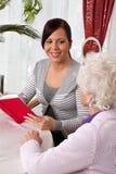 Frau liest zu den Älteren von einem Buch. Lizenzfreies Stockfoto