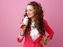 Frau lokalisiert auf trinkendem organischem Jogurt des Bauernhofes des rosa Hintergrundes Stockfoto