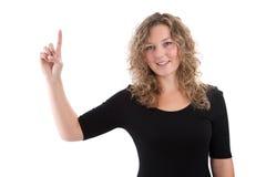 Frau lokalisiert auf Weiß in einem schwarzen Hemd mit dem Fingerzeigen Lizenzfreie Stockfotos