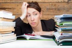 Frau müde geworden vom Arbeiten und vom Studieren nahe bei dem Stapel Stockfotografie