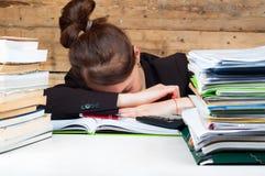 Frau müde geworden vom Arbeiten und vom Studieren nahe bei dem Stapel Lizenzfreie Stockfotografie
