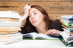 Frau müde geworden vom Arbeiten und vom Studieren nahe bei dem Stapel des Papiers Lizenzfreies Stockfoto