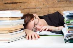 Frau müde geworden vom Arbeiten und vom Studieren nahe bei dem Stapel des Papiers Stockfoto