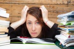 Frau müde geworden vom Arbeiten und vom Studieren nahe bei dem Stapel des Papiers Stockfotos