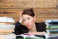 Frau müde geworden vom Arbeiten und vom Studieren nahe bei dem Stapel des Papiers Lizenzfreie Stockfotos