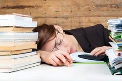 Frau müde geworden vom Arbeiten und vom Studieren nahe bei dem Stapel von papaper Lizenzfreie Stockbilder