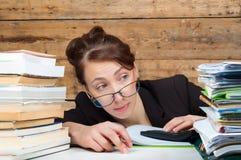 Frau müde geworden vom Arbeiten und vom Studieren nahe bei dem Stapel von papaper Lizenzfreies Stockbild