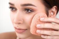 Frau machen eine Gesichtsbehandlung mit einem Schwamm Lizenzfreie Stockbilder