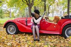 Frau machen Foto mit Auto auf Hintergrund Lizenzfreie Stockbilder