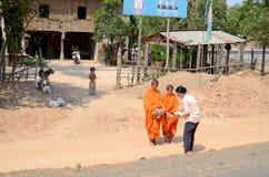 Frau machen Nächstenliebe bei zwei Mönchen Lizenzfreies Stockfoto