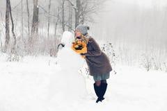 Frau machen Schneemann Stockfoto