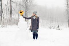 Frau machen Schneemann Lizenzfreie Stockbilder