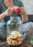 Frau macht Apfelessig - Schalenapfel und schnitt ihn in eine Flasche lizenzfreie stockbilder