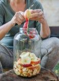 Frau macht Apfelessig - Schalenapfel und schnitt ihn in eine Flasche lizenzfreies stockfoto